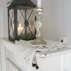 White shelf with lantern and mercury glass candle.