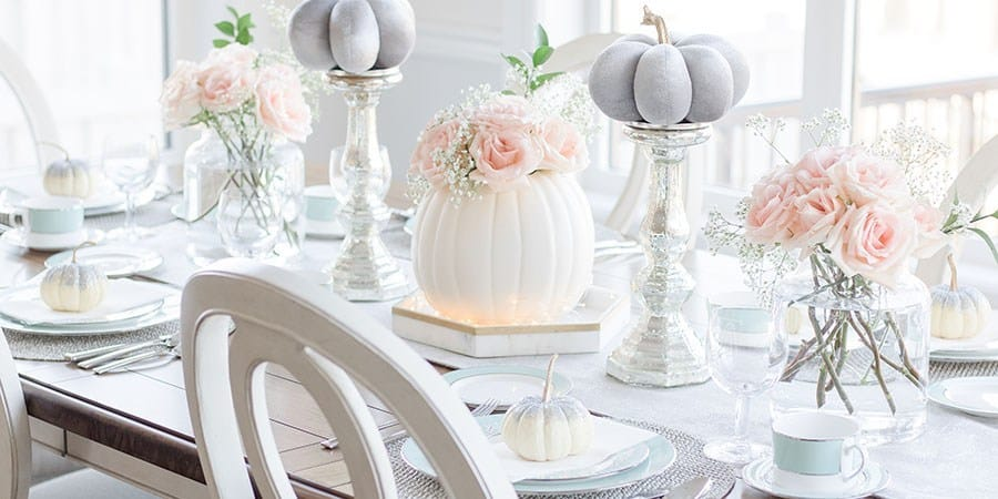 Fall table setting in soft romantic colors with pumpkins and roses