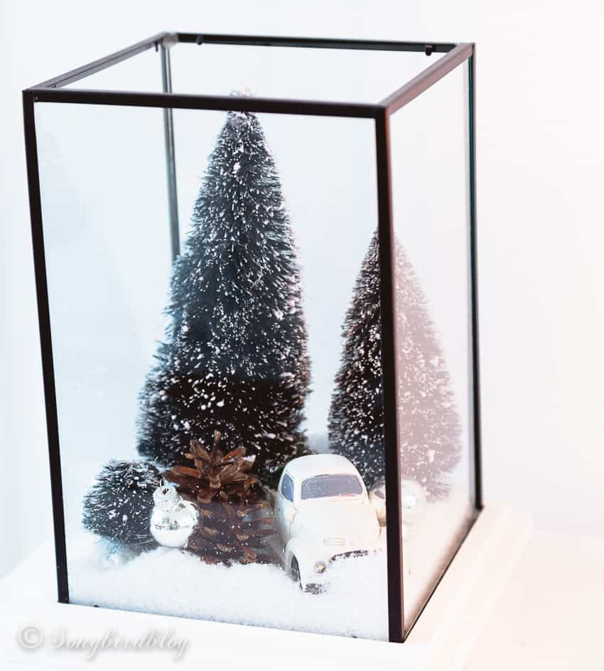 Glass lantern filled with bottle brush trees, fake snow and a little white car