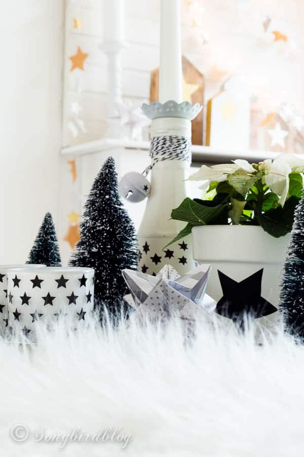 Christmas vignette: a tray with some bottles, candles and a couple of mini Christmas trees. by Songbirdblog.com