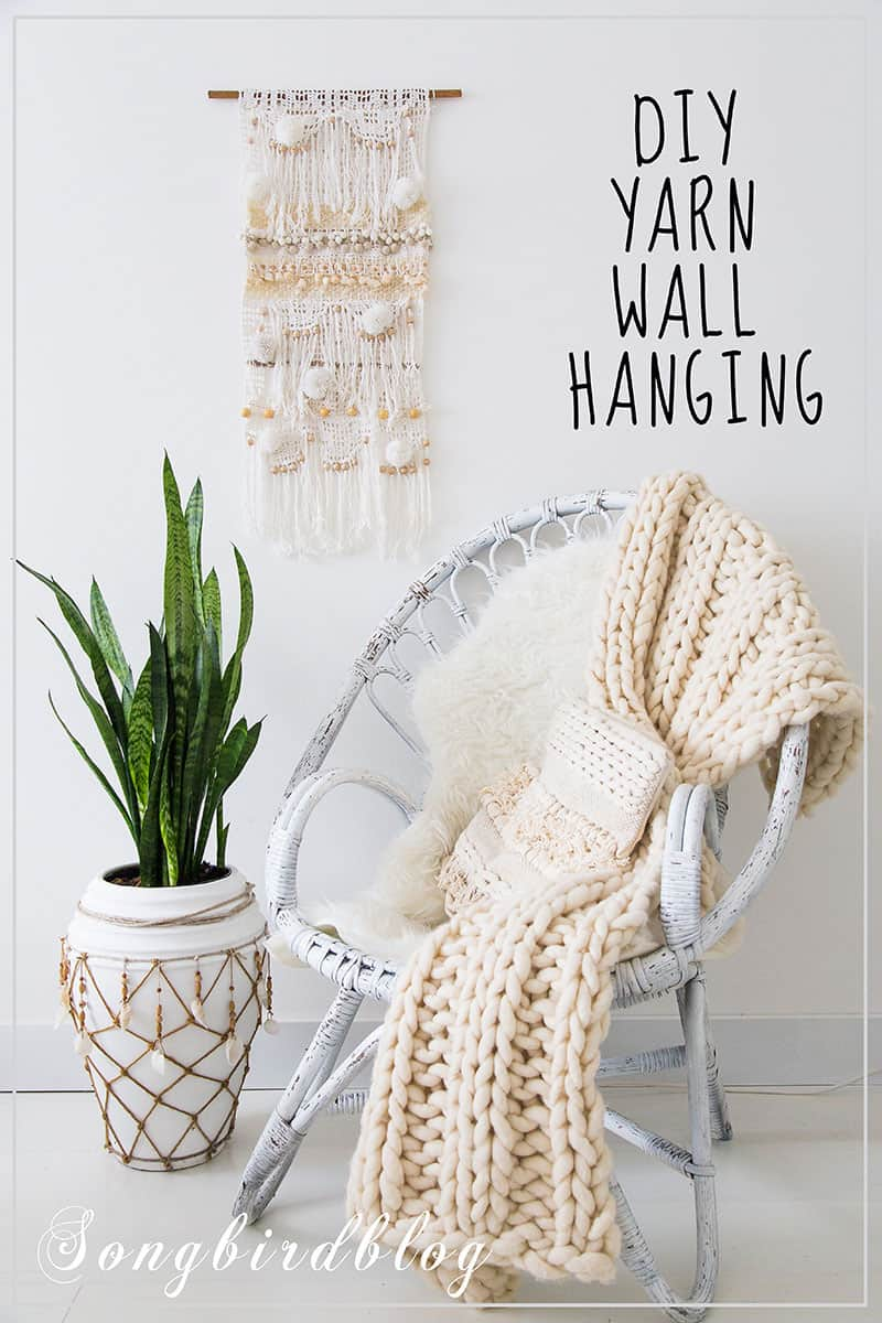 white interior with diy wall hanging on wall behind wicker chair with blanket