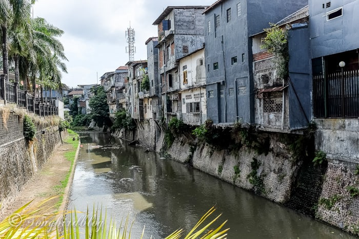 Holiday in Bali. Denpasar street view. Houses on canal