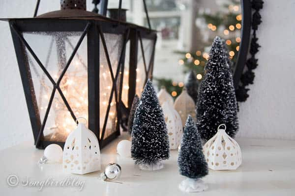 Christmas fairy lights vignette with lantern, mirror and mini trees.