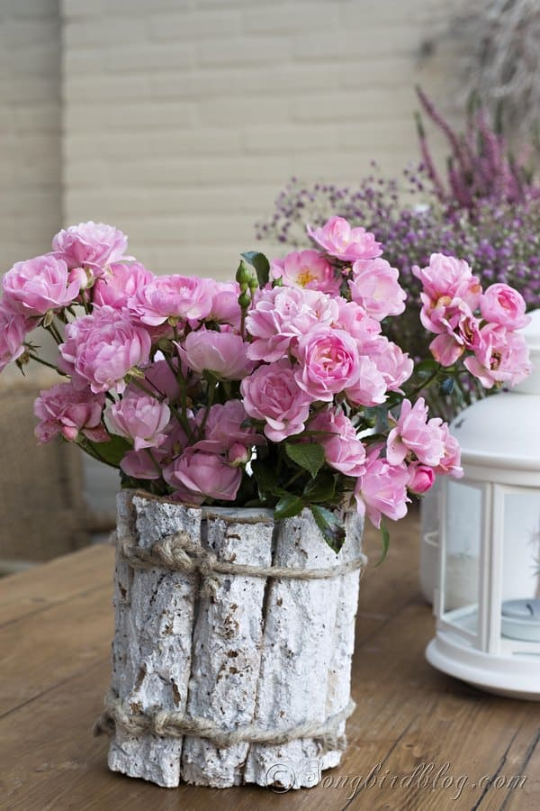 Pink roses in a mason jar that is decorated with pieces of bark. Romantic and rustic flower decoration