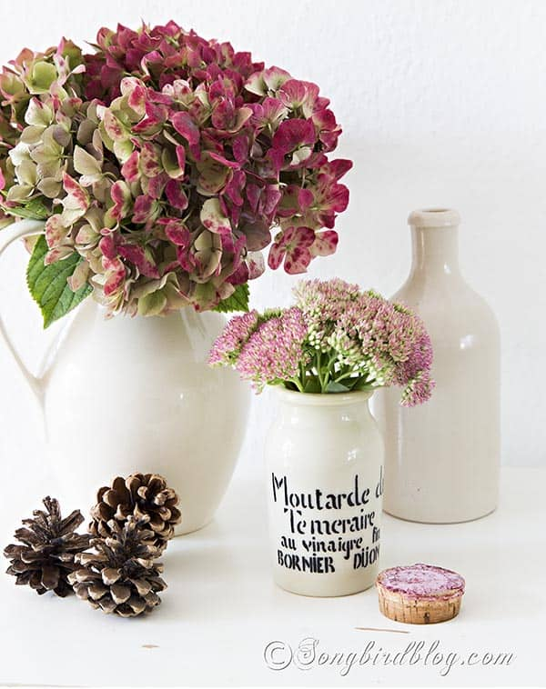 Simple Fall decoration with hydrangea and sedum flowers. The vintage mustard pot and the pine cones add a perfect autumn touch.