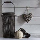 Fall mantel decoration in brown lantern pinecones wicker heart via songbirdblog.com