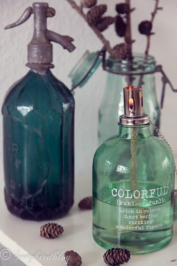 Green Vintage Bottles Fall Decor with an oil lamp and pine cones