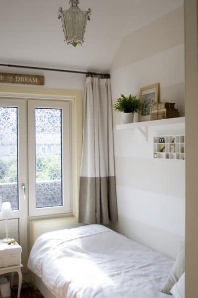small guest room with striped walls, suitcase nightstand and billy built-in