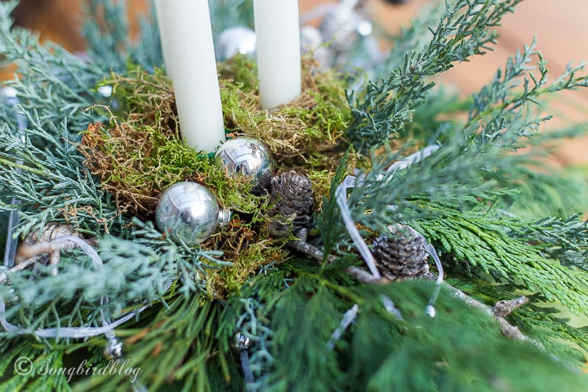 close up of Christmas centerpiece with moss and ornaments
