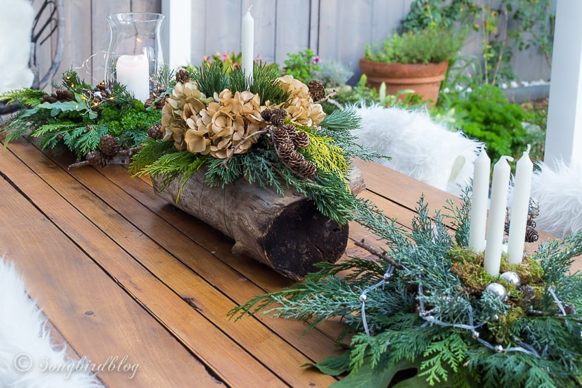 garden table with three fresh  homemade Christmas centerpieces