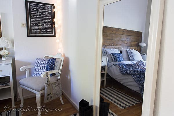 Ikea Hemnes mirror in bedroom with reclaimed wood headboard, blue bedding and a DIY upholstered chair