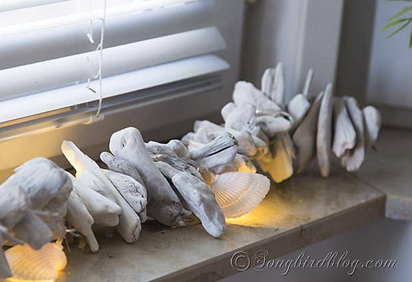 Nauticial beach bedroom decor on window sill. Drift wood garland with string of lights made with shells.