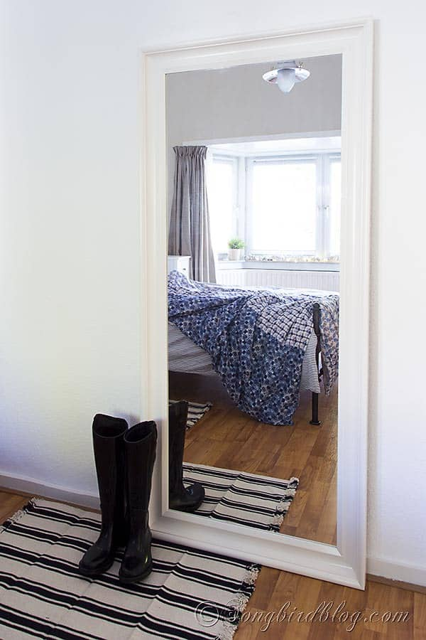 Black boots in front of a large mirror in bedroom with blue bedding