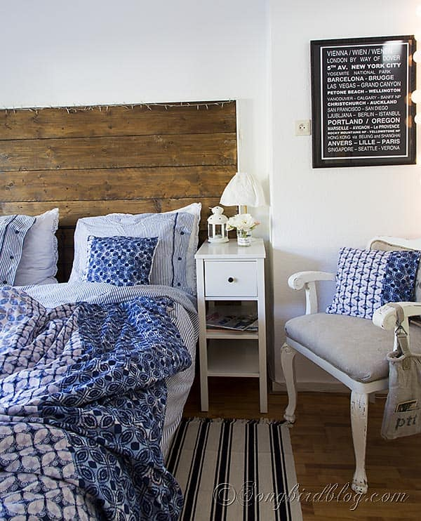 Ikea Hemnes mirror in bedroom with reclaimed wood headboard and blue bedding