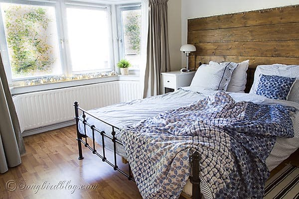 bedroom with repurposed wood headboard and blue bedding
