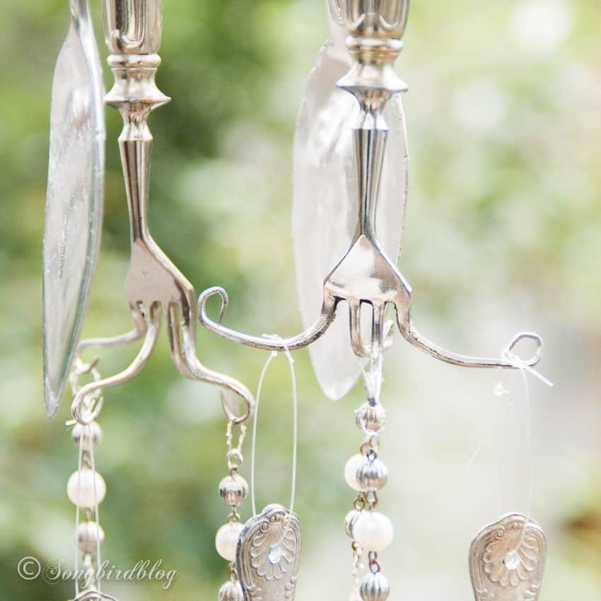 Closeup of twisted forks and flattened spoons in silverware wind chime.