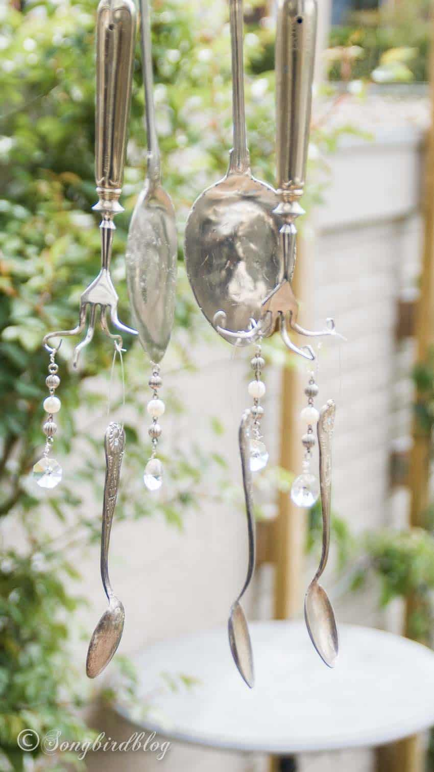 wind chime made from silverware hanging in garden