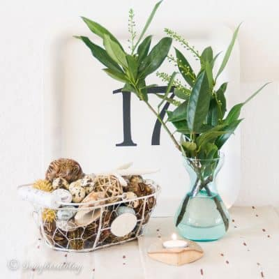 Spring decorating on a budget with green leaves in a vase and a basket with Easter decorations
