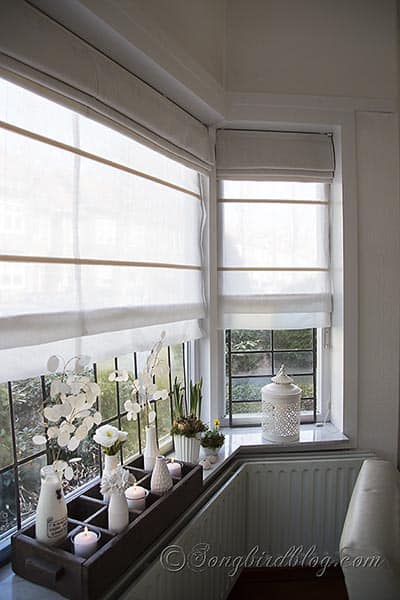 bay window with double layered roman shades