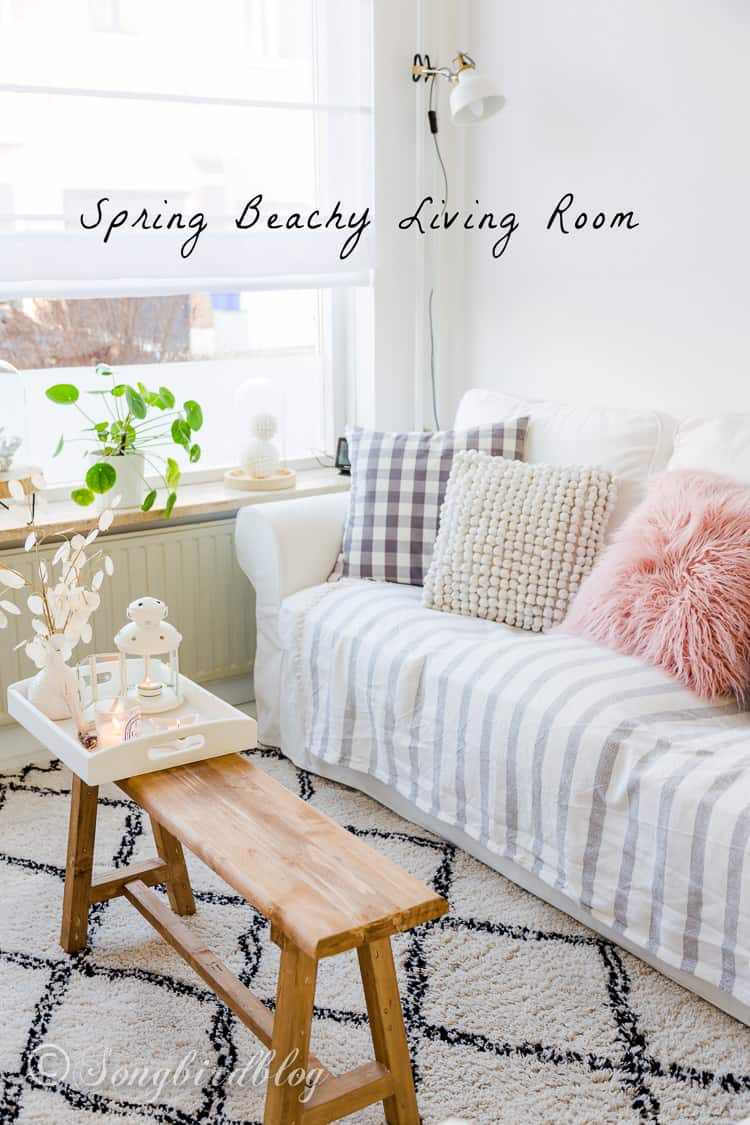 A bright, white living room breathing a touch of Spring. The coastal stripes and white couch with pastel throw pillows give this sitting area a beach house vibe.