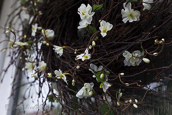 Using faux flowers to decorate a twig wreath is the fastest and easiest way to create a Spring wreath for your front door. www.songbirdblog.com