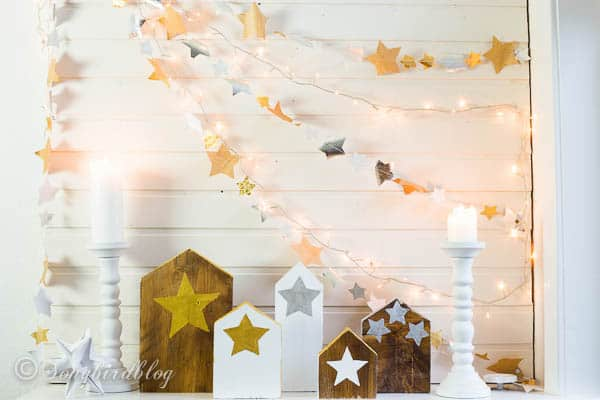Christmas mantel with paper stars garlands and wood block houses