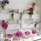 bottles with flowers on a pallet wood summer mantel