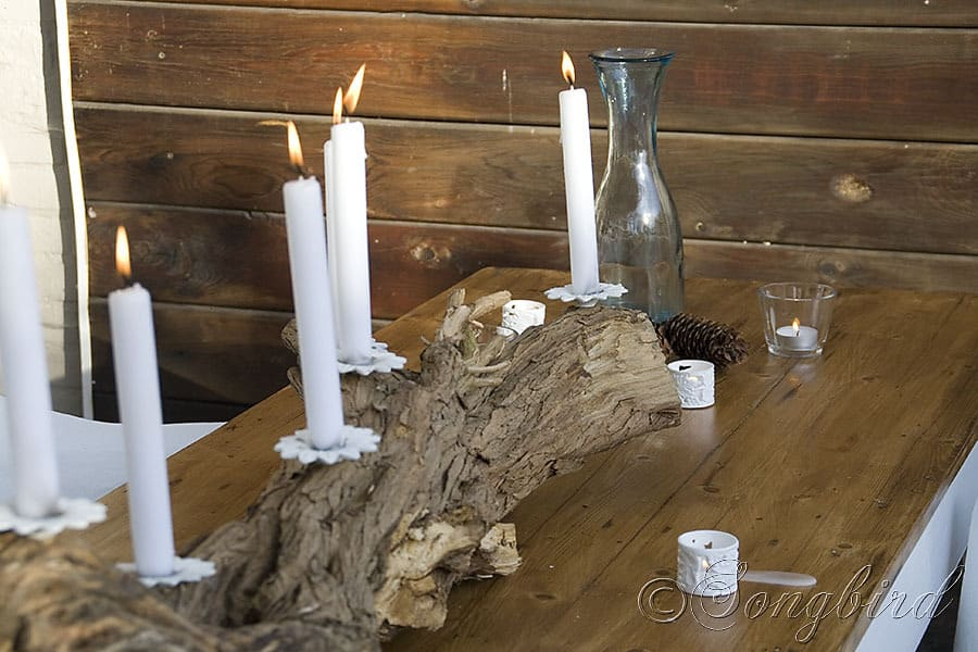 stick made from a repurposed tree trunk and chandelier parts