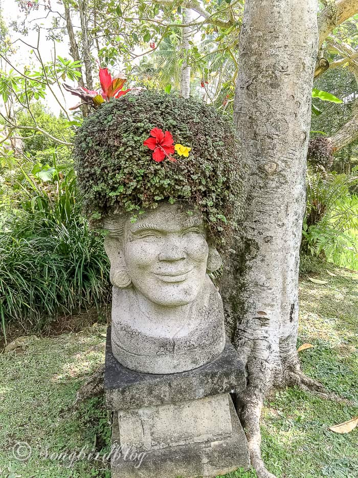 Holiday in Bali. Ubud village. Statue with green wig