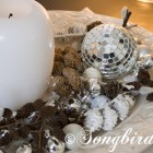 Christmas decoration in white, silver and browns with pine cones and disco ball