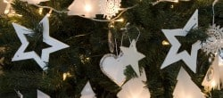 Christmas tree in white with homemade ornaments and lights from paper, wood and fabric