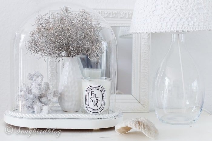A bit of coastal beach decor with a vintage glass dome that is turned into a nautical cloche.