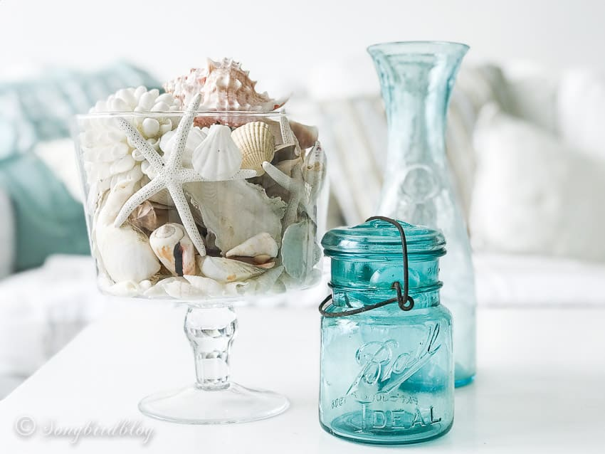 Beach style decor with shells in blue glass
