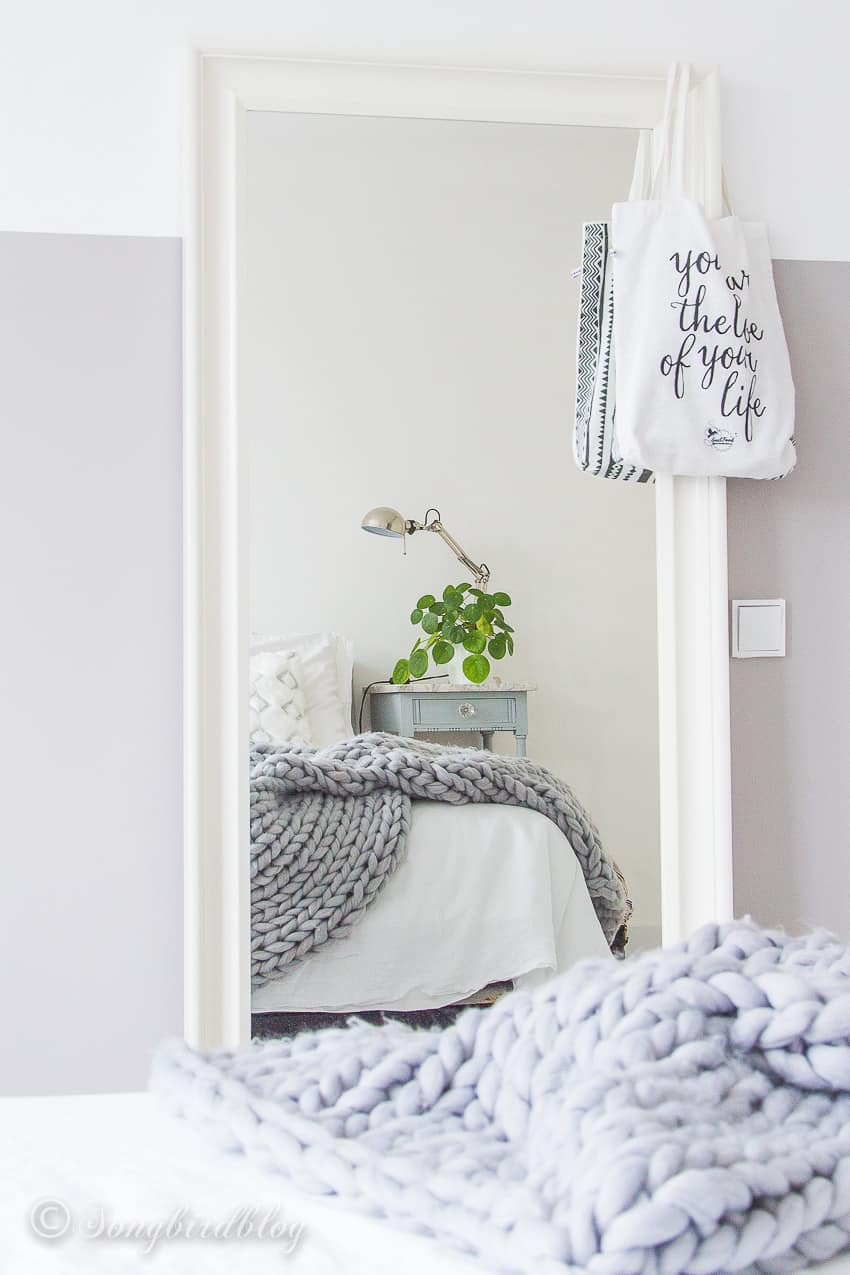 Grey bedroom styling with dresser, mirrors and balloons hanging from ceiling
