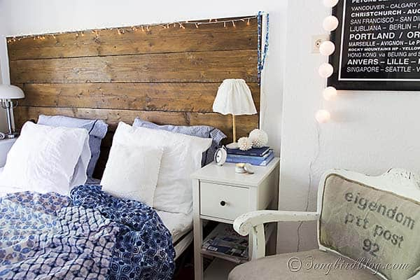 bedroom in blue and white with a reclaimed wood headboard and white bed linen with a blue bed spread