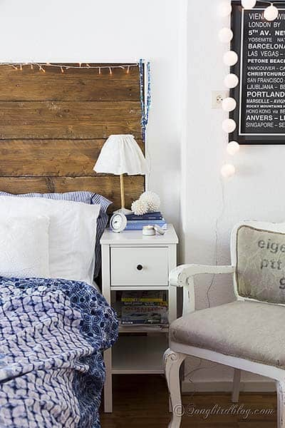 bedroom with a reclaimed wood headboard and white bed linen with a blue bed spread
