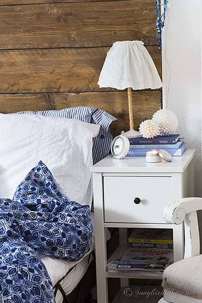 bedroom with a reclaimed wood headboard and white bed linen with a blue blanket