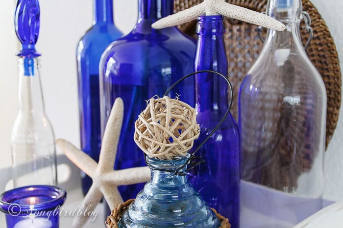 Beach decor with blue glass bottles.