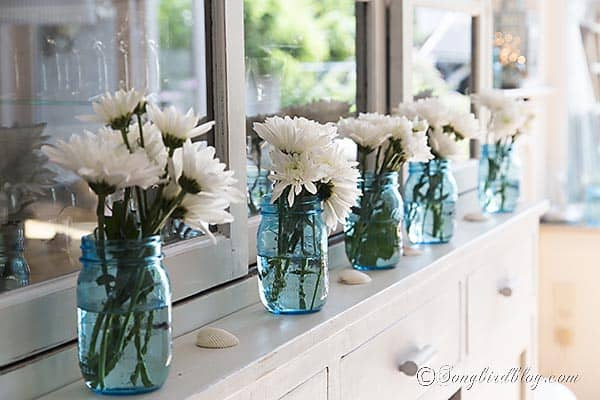 decorating with blue mason bell jars and flowers http://songbirdblog.com