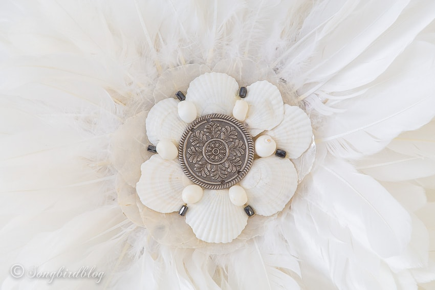 DIY wall hanging with feathers and shells in bohemian coastal style