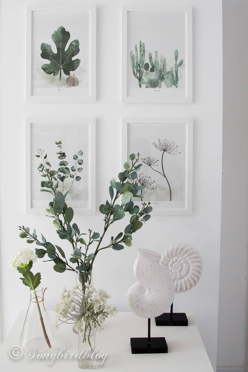 four framed botanical prints with matching faux branches