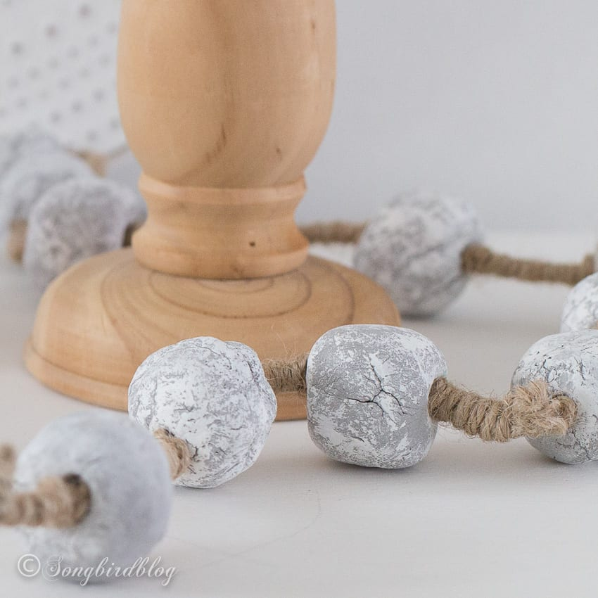 cement bead garland draped around wooden candle stick