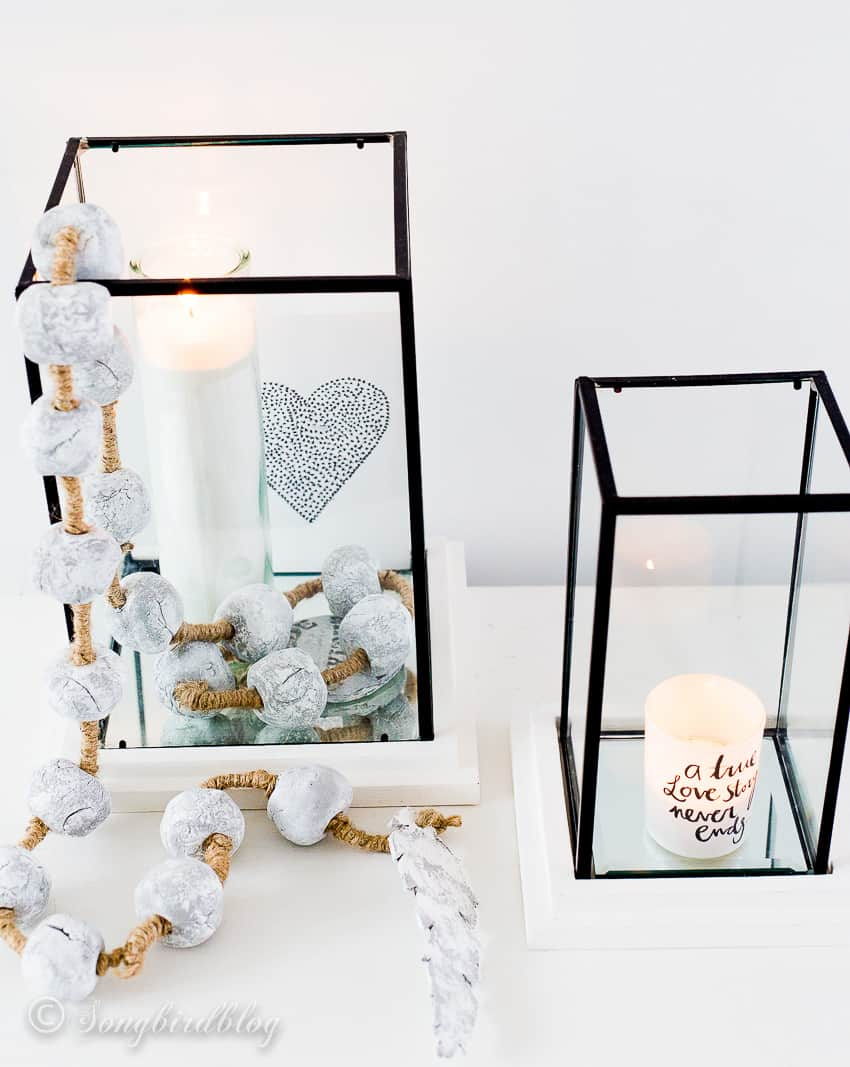 two glass square hurricanes with candles and a cement bead garland draped over it