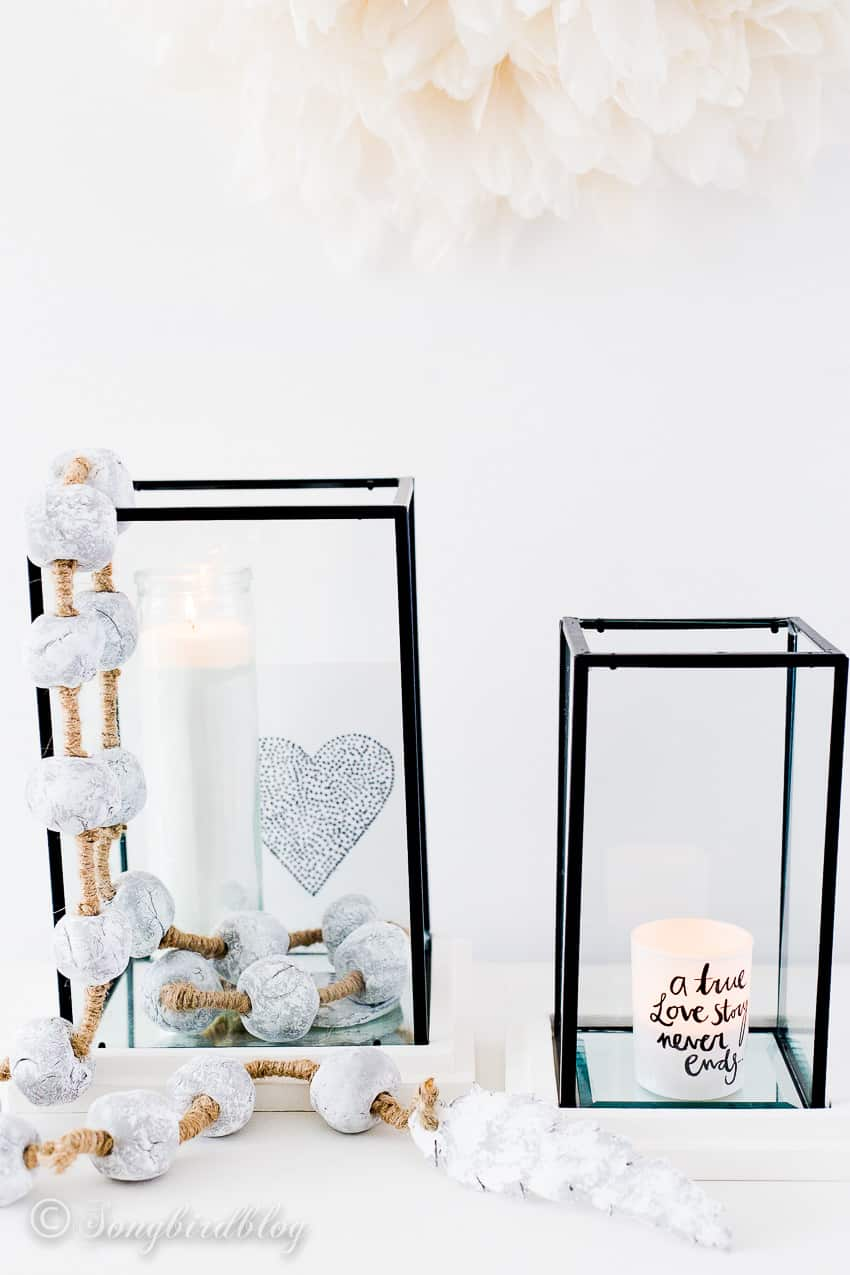 white decorations with two hurricanes, candles and cement bead garland