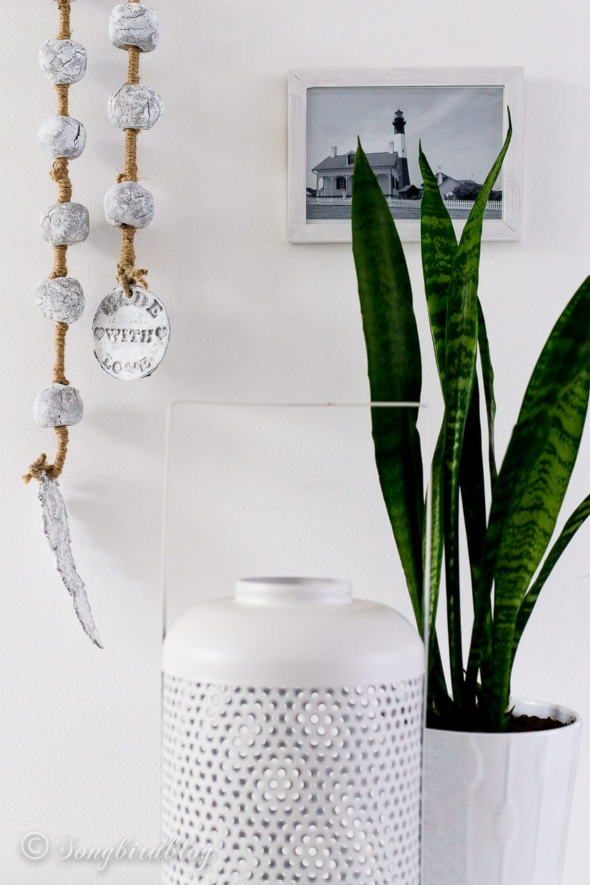 cement bead garland hanging on white wall flanked by lantern and green plant