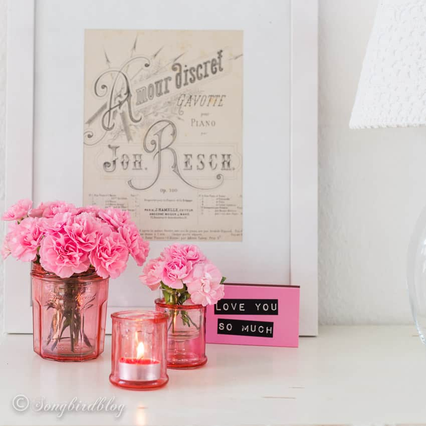 Romantic decoration with pink flowers in diy tinted mason jars in front of a frame with vintage sheet music