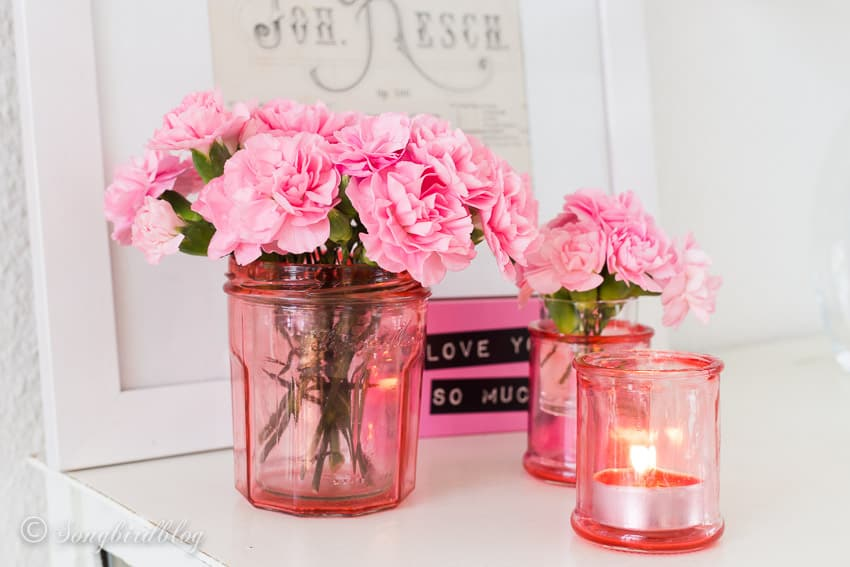 pink decoration with flowers and diy colored glass jars