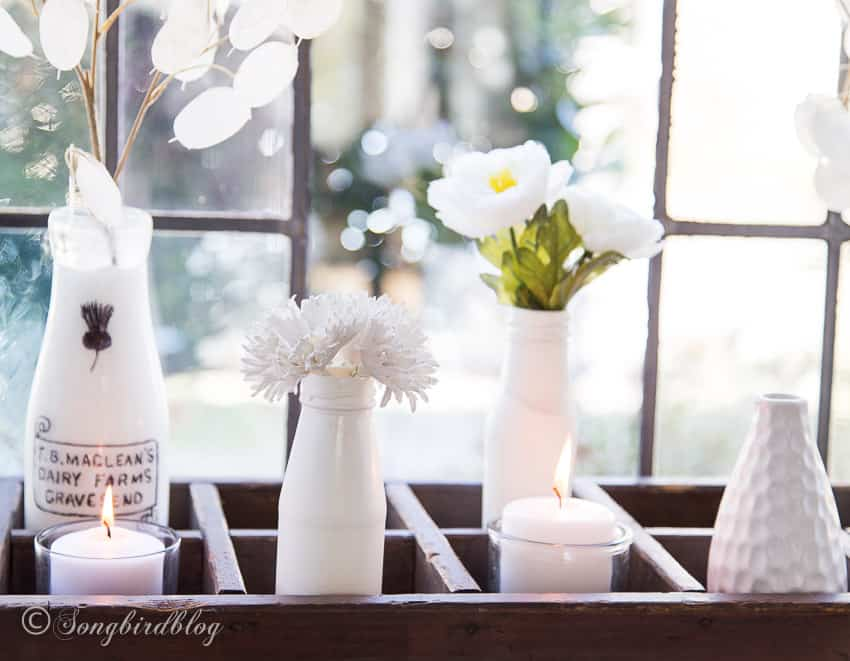 close up white decorations in crate on window sill
