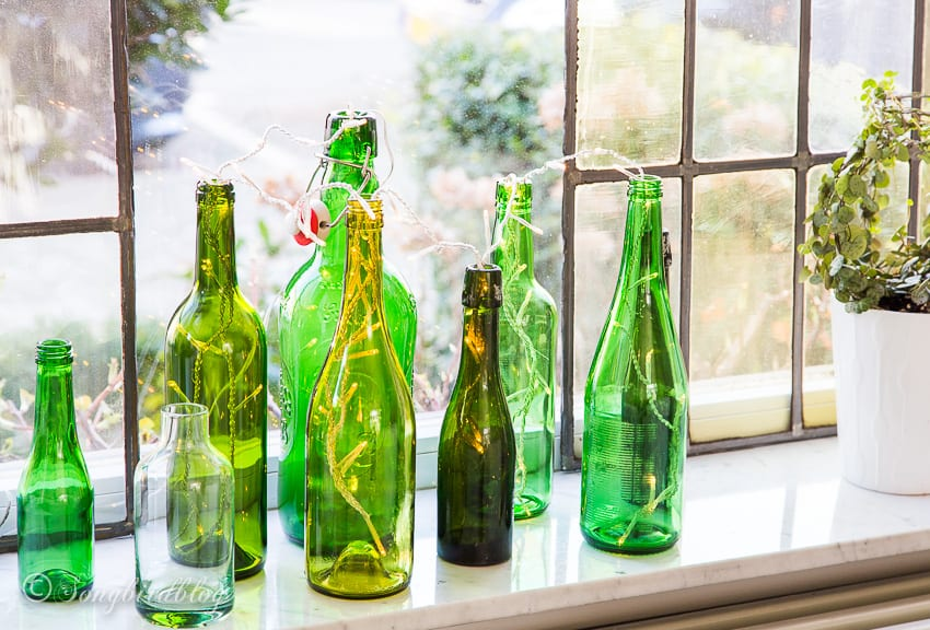 green bottles with sting of light on window sill
