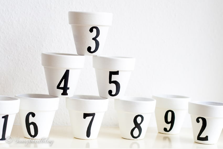 Collection of white painted terra cotta pots with numbers